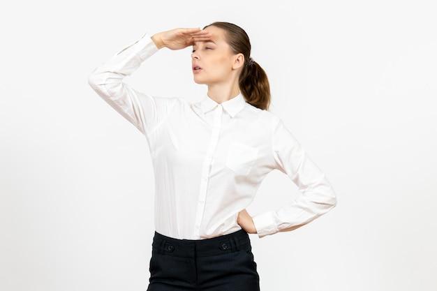 Vue de face jeune femme en blouse blanche regardant à distance sur fond blanc travail de bureau émotion féminine modèle de sentiment