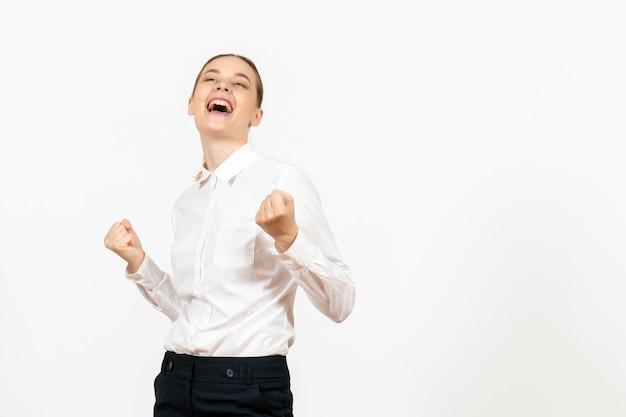 Vue de face jeune femme en blouse blanche avec un visage joyeux sur fond blanc job office modèle de sentiment d'émotion féminine