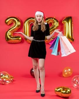 Vue de face jeune femme avec bonnet de noel tenant des ballons de sacs à provisions sur rouge