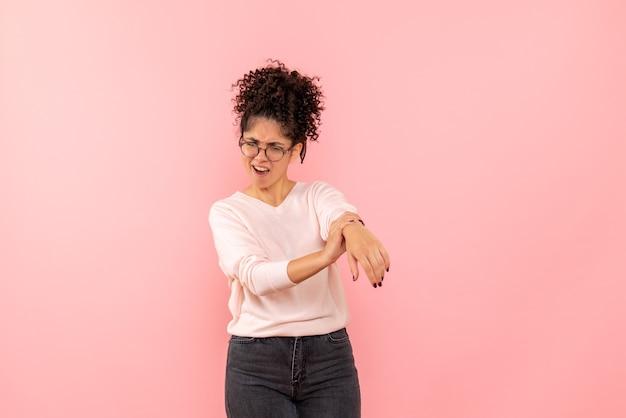 Vue de face de la jeune femme avec bras blessé sur le mur rose
