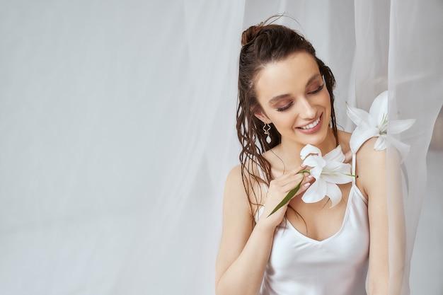Vue de face de la jeune femme brune avec un maquillage parfait, une peau propre et une fleur de lys sur l'épaule. portrait de jeune fille souriante aux cheveux mouillés posant sur fond blanc entre tulle. concept de beauté.
