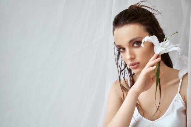 Vue de face de la jeune femme brune avec un maquillage parfait et un visage fort tenant une fleur de lys blanc. portrait de jeune fille aux cheveux mouillés posant sur fond blanc entre tulle le matin. concept de beauté.