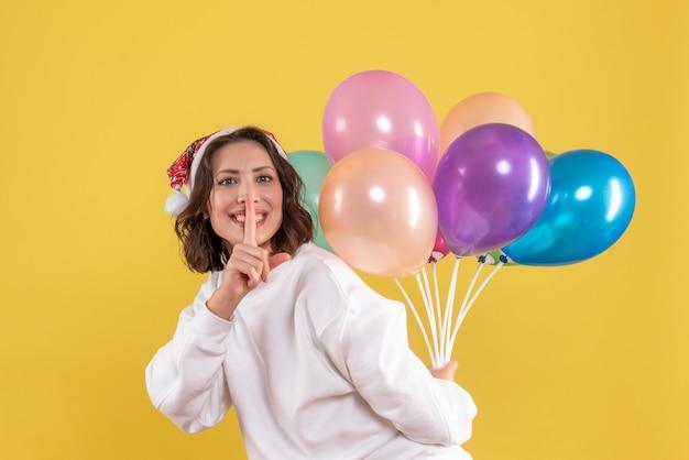 Vue de face jeune femme cachant des ballons colorés sur le bureau jaune nouvel an noël couleur vacances femme émotion