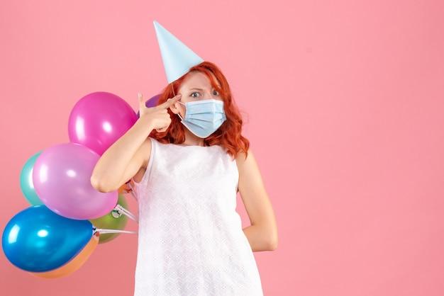 Vue de face jeune femme cachant des ballons colorés dans un masque stérile sur fond rose partie covid- couleur du nouvel an de noël