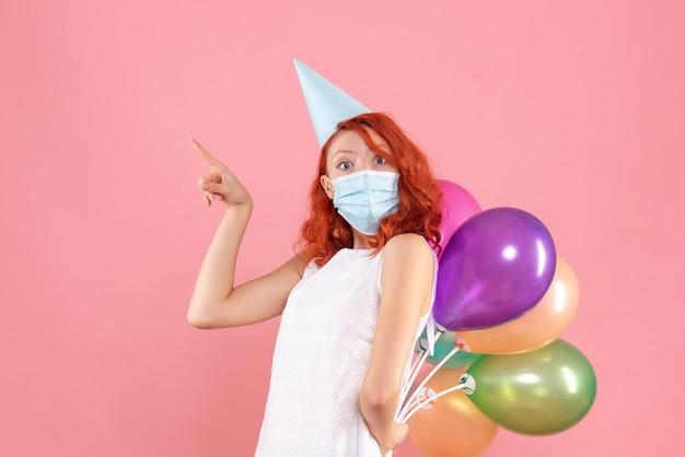 Vue de face jeune femme cachant des ballons colorés dans un masque stérile sur le fond rose partie covid- couleur de noël du nouvel an