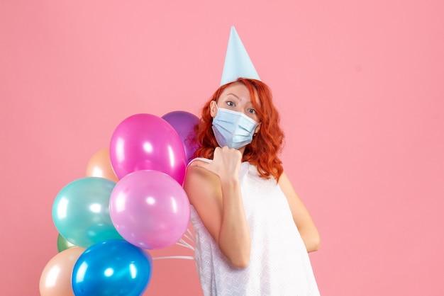 Vue de face jeune femme cachant des ballons colorés derrière son dos dans un masque stérile sur le plancher rose partie covid- couleur du nouvel an de noël