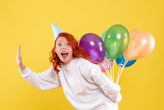 Vue de face jeune femme cachant des ballons colorés derrière son dos sur un fond jaune couleur nouvelle année