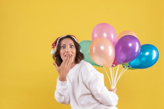 Vue de face jeune femme cachant des ballons colorés nouvel an noël couleur vacances femme émotion