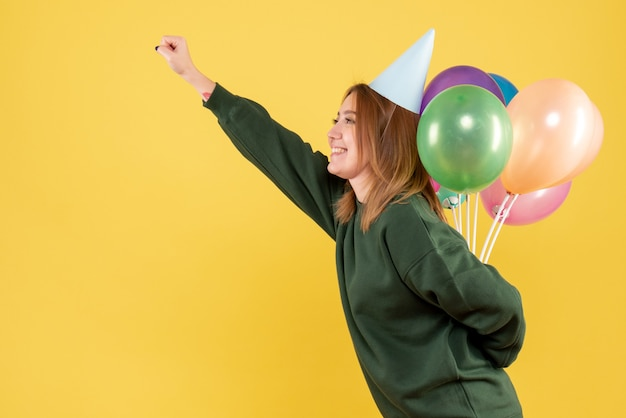 Vue de face jeune femme cachant des ballons colorés