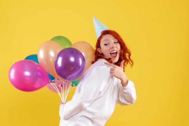 Vue de face jeune femme cachant de jolis ballons colorés sur jaune