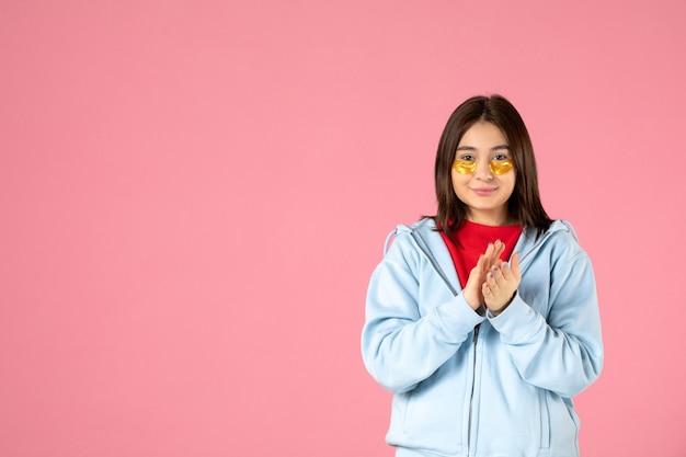 Vue de face d'une jeune femme avec des cache-œil frappant sur un mur rose