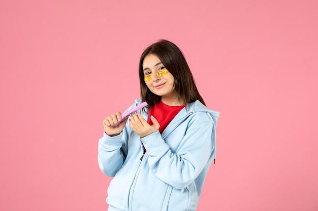 Vue de face d'une jeune femme avec des cache-œil et une lime à ongles sur un mur rose