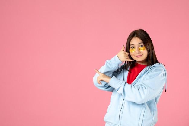 Vue de face d'une jeune femme avec des cache-œil sur un mur rose
