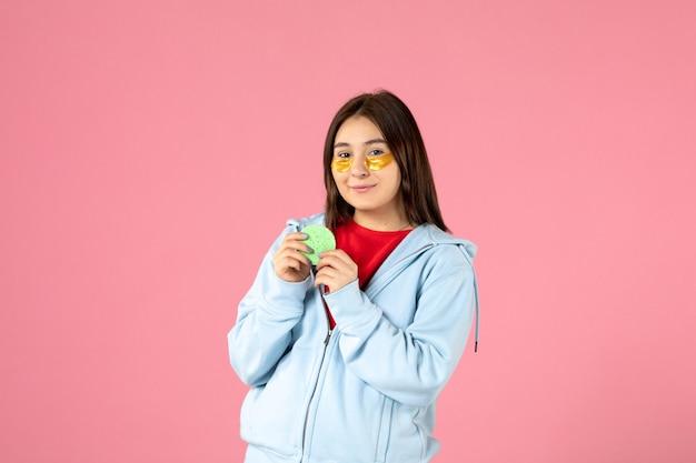 Vue de face d'une jeune femme avec des cache-œil et une petite éponge sur un mur rose
