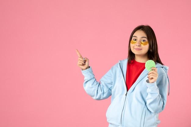 Vue de face d'une jeune femme avec des cache-œil et une petite éponge de peau sur un mur rose