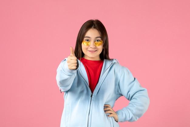 Vue de face d'une jeune femme avec des cache-œil sous ses yeux sur un mur rose