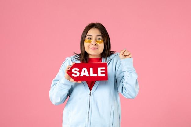 Vue de face d'une jeune femme avec des cache-œil tenant une bannière de vente sur un mur rose
