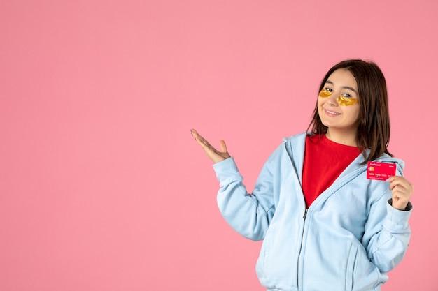 Vue de face d'une jeune femme avec des cache-œil tenant une carte bancaire sur un mur rose