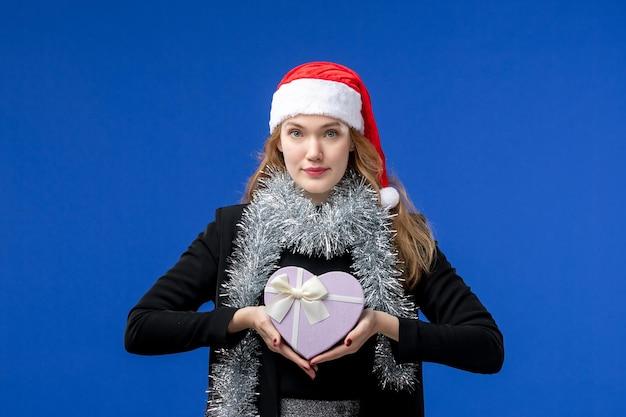 Vue de face de la jeune femme avec le cadeau du nouvel an sur le mur bleu