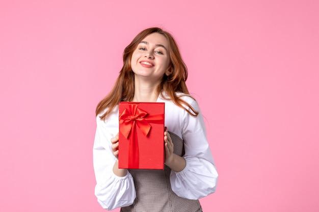 Vue de face jeune femme avec cadeau en emballage rouge sur fond rose date de l'amour mars cadeau sensuel horizontal femme parfum photo argent égalité
