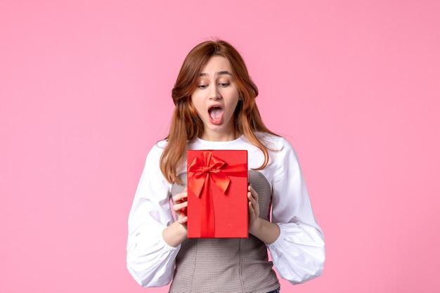 Vue de face jeune femme avec cadeau en emballage rouge sur fond rose mars cadeau sensuel horizontal photo argent égalité femme parfum