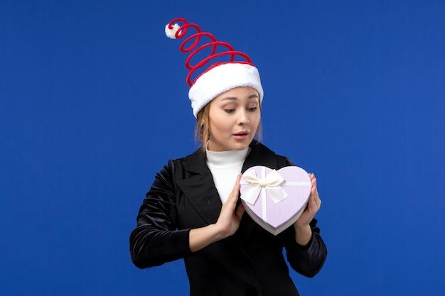 Vue de face jeune femme avec cadeau en forme de coeur sur le mur bleu des cadeaux de vacances de nouvel an