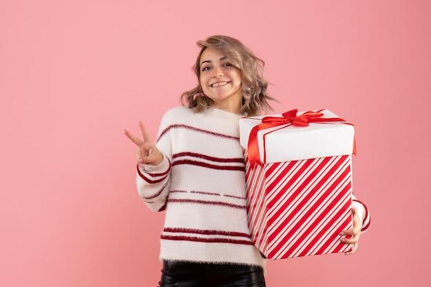 Vue de face jeune femme avec cadeau de noël