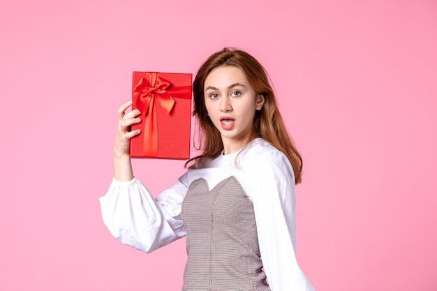 Vue de face jeune femme avec cadeau en paquet rouge sur fond rose amour date mars égalité sensuelle horizontale femme argent photo