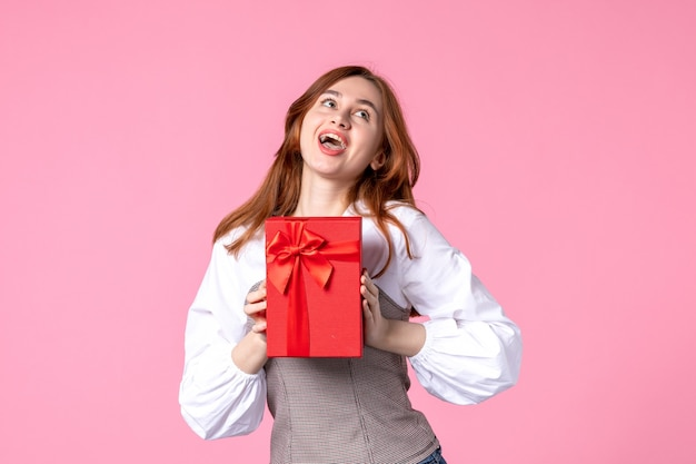 Vue de face jeune femme avec cadeau en paquet rouge sur fond rose date de l'amour mars cadeau sensuel horizontal de l'égalité de l'argent photo parfum