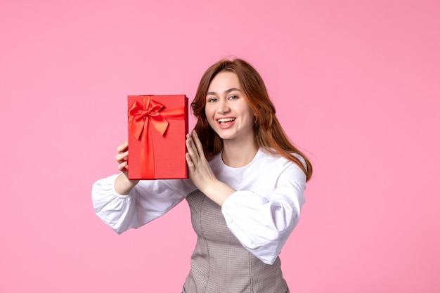Vue de face jeune femme avec cadeau en paquet rouge sur fond rose date d'amour mars cadeau sensuel horizontal femme parfum photo argent