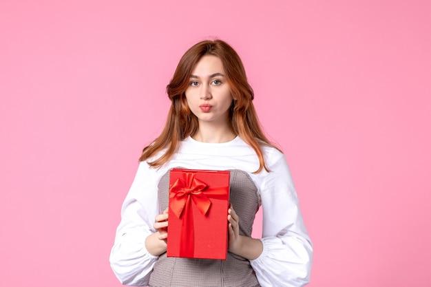 Vue de face jeune femme avec cadeau en paquet rouge sur fond rose date d'amour mars cadeau sensuel horizontal femme parfum photos égalité de l'argent