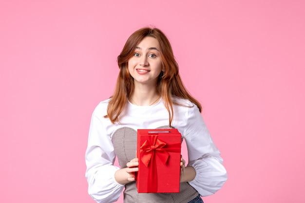 Vue de face jeune femme avec cadeau en paquet rouge sur fond rose date d'amour mars cadeau sensuel horizontal femme photo argent égalité