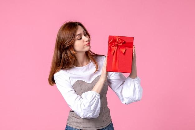 Vue de face jeune femme avec cadeau en paquet rouge sur fond rose mars argent femme sensuelle horizontale cadeau parfum égalité