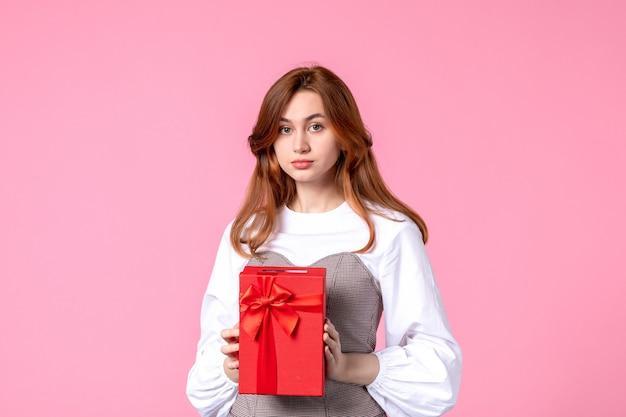 Vue de face jeune femme avec cadeau en paquet rouge sur fond rose mars cadeau sensuel horizontal parfum photos femme égalité de l'argent