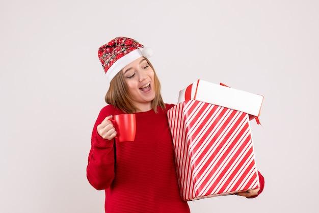 Vue de face jeune femme avec cadeau et tasse de thé