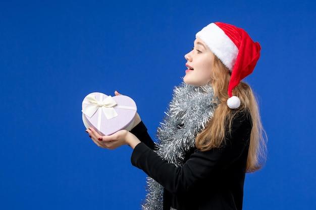 Vue de face d'une jeune femme avec un cadeau de vacances sur le mur bleu