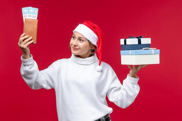 Vue de face jeune femme avec des cadeaux et des billets sur fond rouge