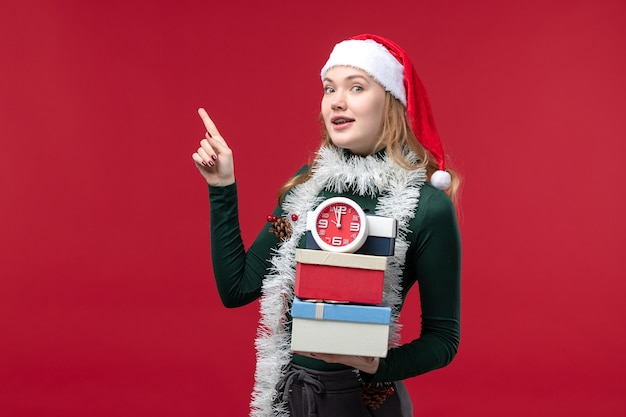 Vue de face jeune femme avec des cadeaux avec horloge sur un bureau rouge