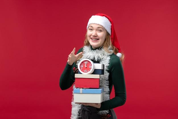 Vue de face jeune femme avec des cadeaux avec horloge sur fond rouge clair