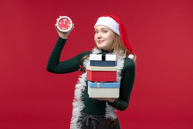 Vue de face jeune femme avec des cadeaux et horloge sur fond rouge