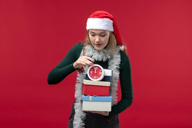Vue de face jeune femme avec des cadeaux avec horloge sur fond rouge