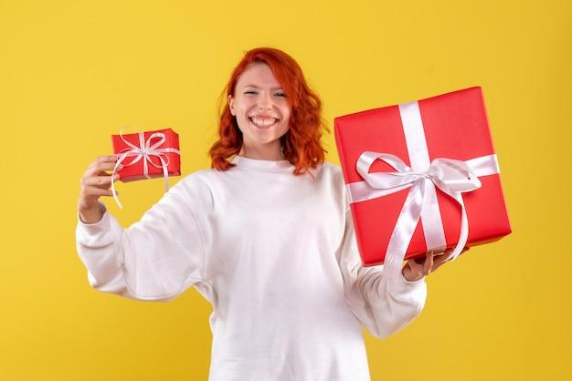 Vue de face de la jeune femme avec des cadeaux de noël sur mur jaune