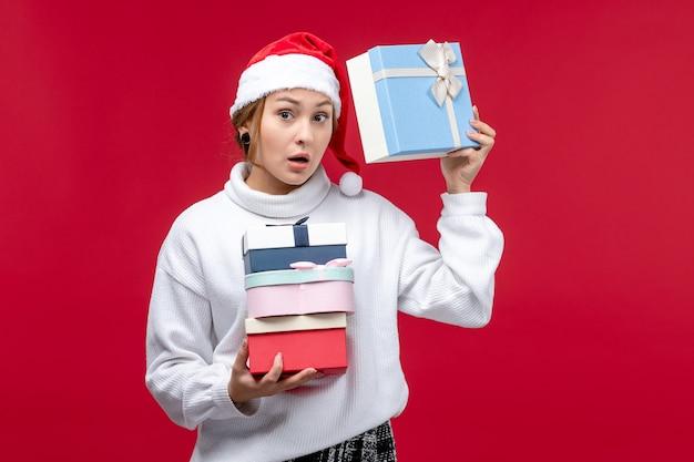Vue de face jeune femme avec des cadeaux de vacances sur fond rouge