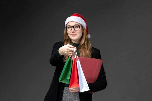 Vue de face jeune femme avec des cadeaux de vacances sur un mur sombre cadeau de nouvel an