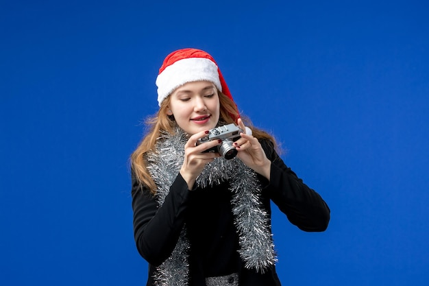 Vue de face de la jeune femme avec caméra sur mur bleu