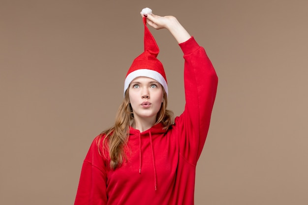 Vue de face jeune femme avec cape rouge sur fond marron vacances d'émotion de noël