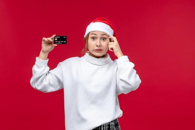 Vue de face jeune femme avec carte bancaire sur un bureau rouge