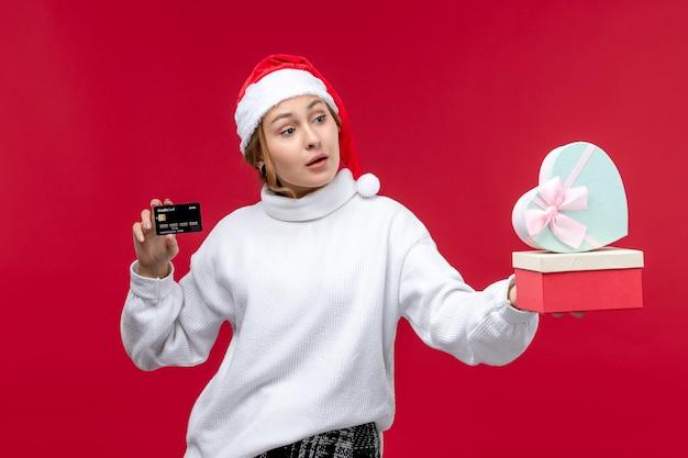 Vue de face jeune femme avec carte bancaire et cadeaux sur un bureau rouge