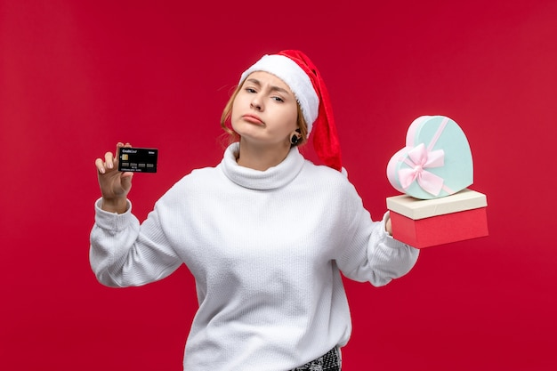 Vue de face jeune femme avec carte bancaire et cadeaux sur fond rouge