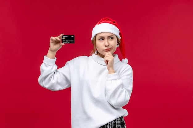 Vue de face jeune femme avec carte bancaire sur fond rouge